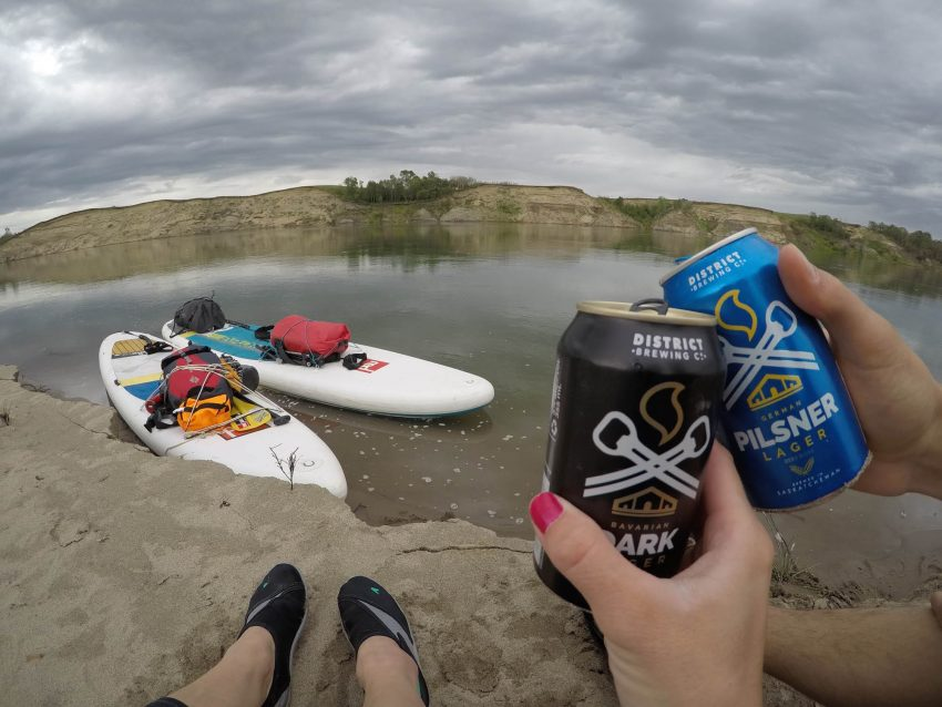 Cheersing two cans of District Brewing on the shore