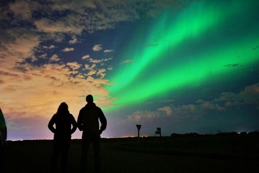 Couple looking up at the Northern Lights