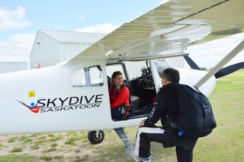 Female sitting in plane ready to go skydiving