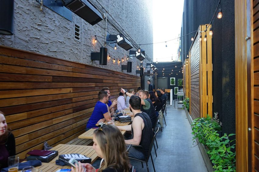 View of the Una Pizza patio with wood slates on the walls