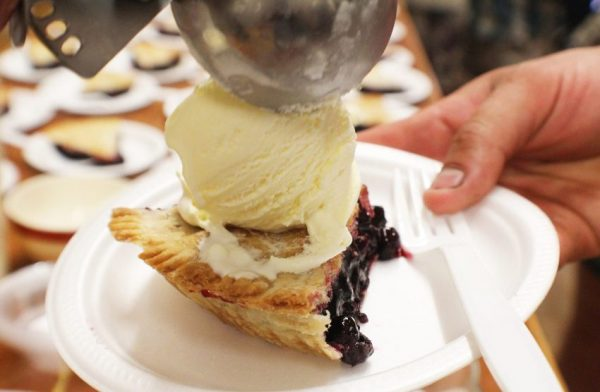 Saskatoon Berry pie with a scoop of vanilla ice cream on a Styrofoam plate with a plastic fork.