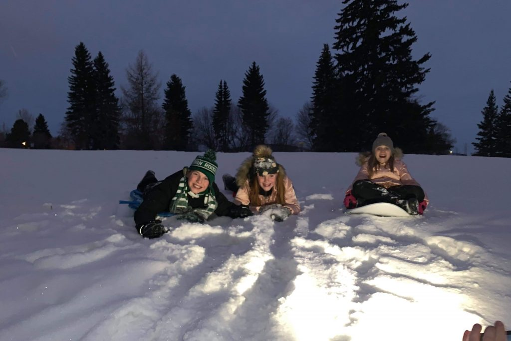 Three children laying in the snow in the evening time