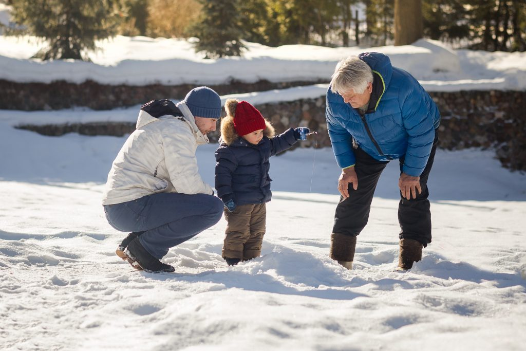Grandfather, Father and Son Ice Fishing in Winter
