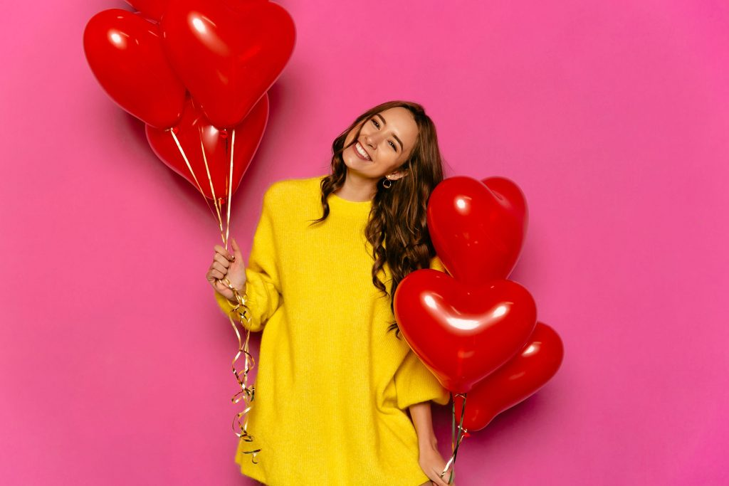 Women in yellow holding a bunch of heart shaped Valentine's Day balloons
