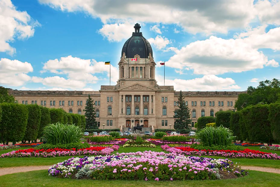 Cloudy blue sky backdrop of the Legislative building in Regina Saskatchewan surrounded by a bed of flowers.