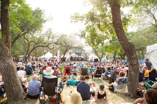 People sitting down under trees watching a performance at the Regina Folk Festival.