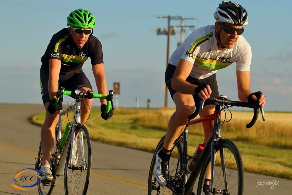 Two cyclists racing on a paved road in Saskatchewan.