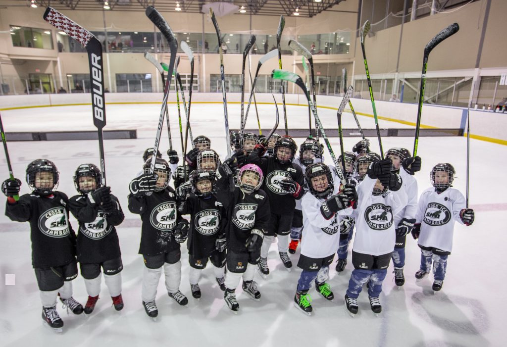 Young hockey players on the Cross Ice Jamboree Team raising their hockey in an indoor ice rink.