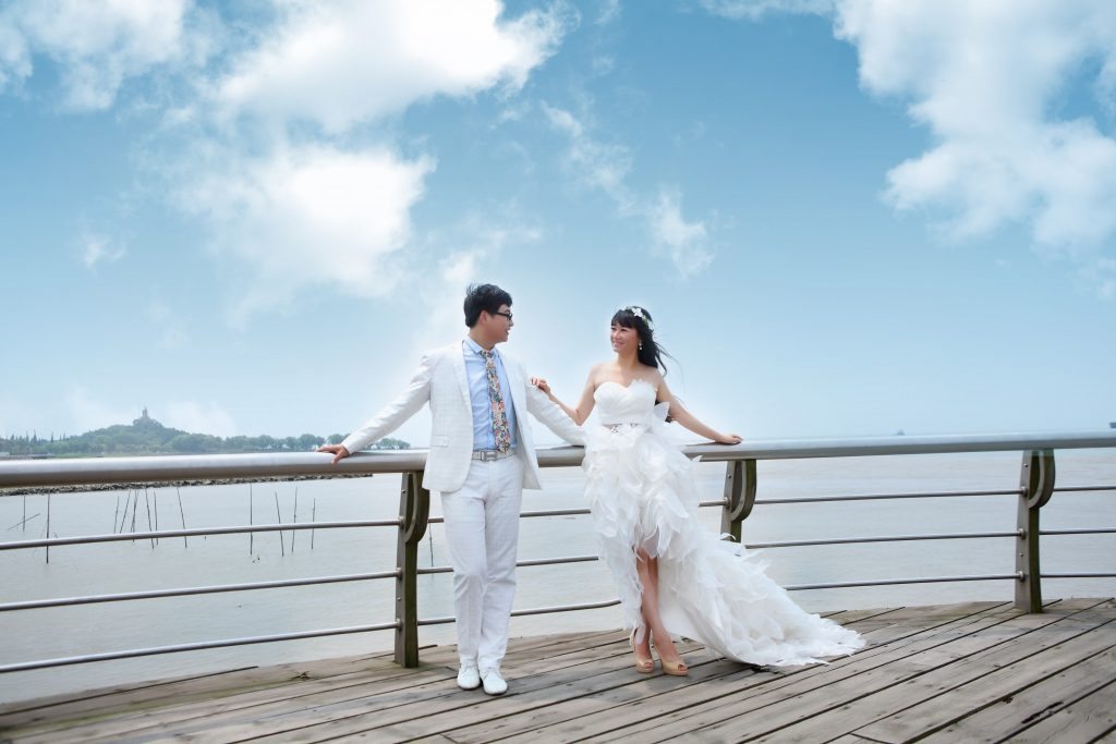 Bride and groom on a bridge overlooking a lake.