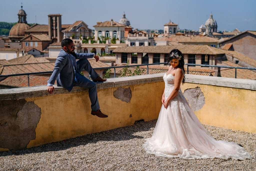 Bride and groom on a rooftop overlooking Rome.