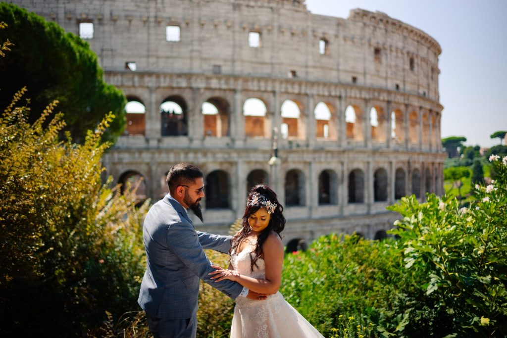 Bride and groom standing on a hilltop across from the Colosseum in Rome.