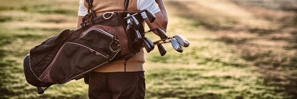 Man with golf clubs on the golf course
