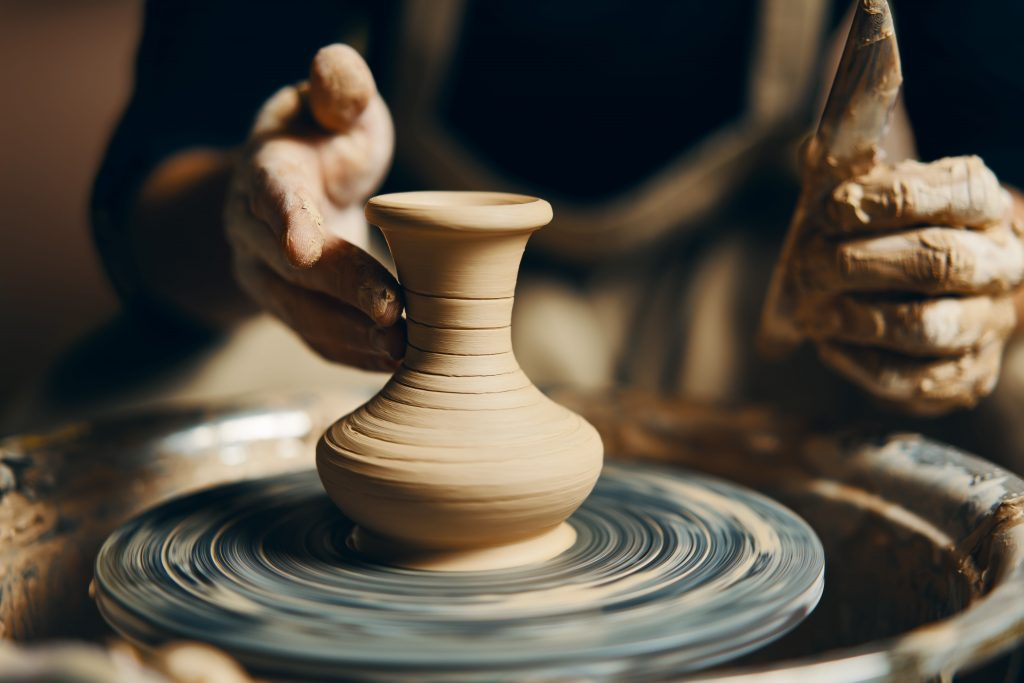 Molding a vase out of clay on a potter's wheel