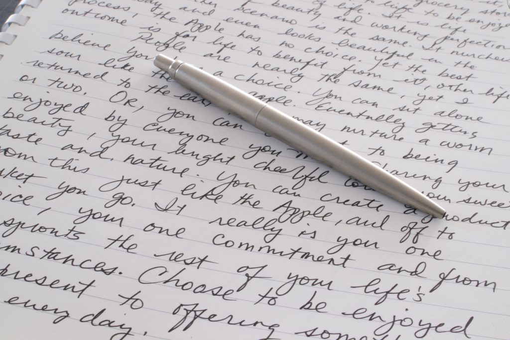 Pen and paper with cursive writing