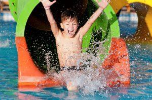 Boy splashing into water from waterslide