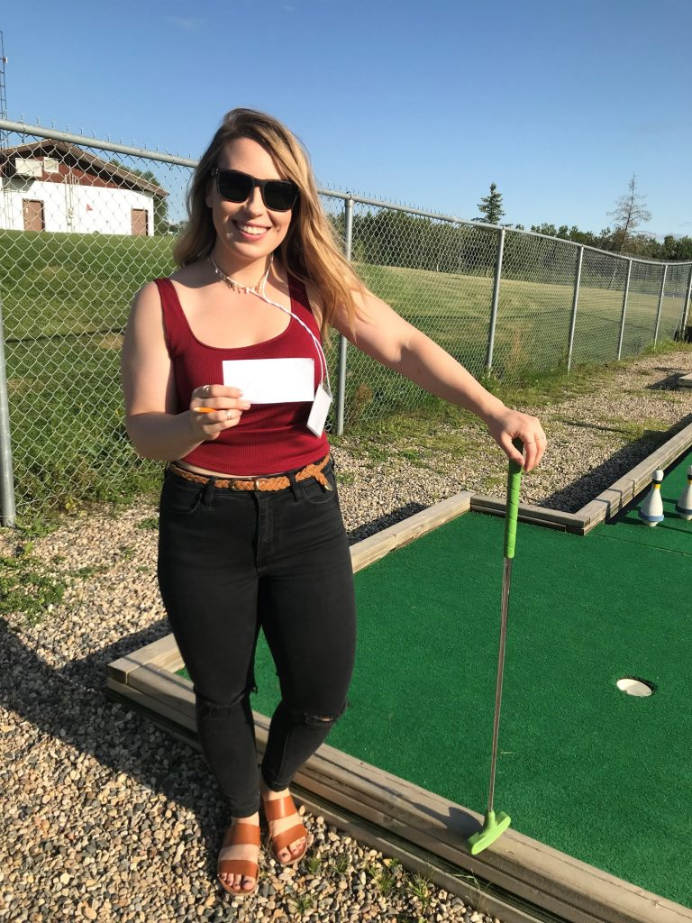 Ashley Herchak at mini golf course holding putter