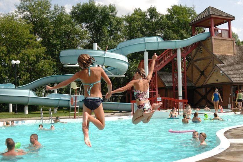 Pike Lake Water Park - Two kids jumping into pool with waterslide in background