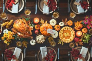 Overhead view of fall dinner with food and decor on table