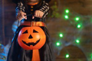 Little Girl in Halloween Costume Holding Pumpkin